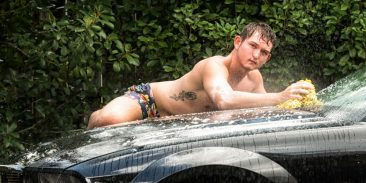 Male model laying on his car while he washes it.