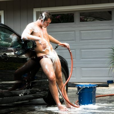 Male model playing with a water hose.