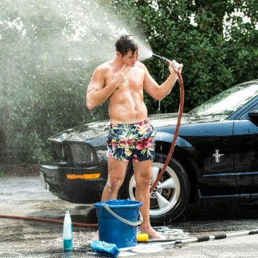 Sexy guy spraying himself with a water hose while he washes his car.