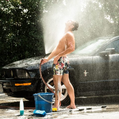 Male model washing his car for a photo shoot.