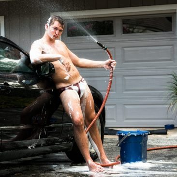 Young guy in a swimsuit washing his car.