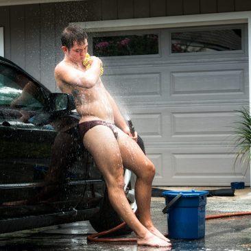 Guy washing himself while washing his car.