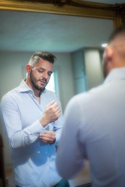 Guy getting dressed in mirror | Trey Fox Photography